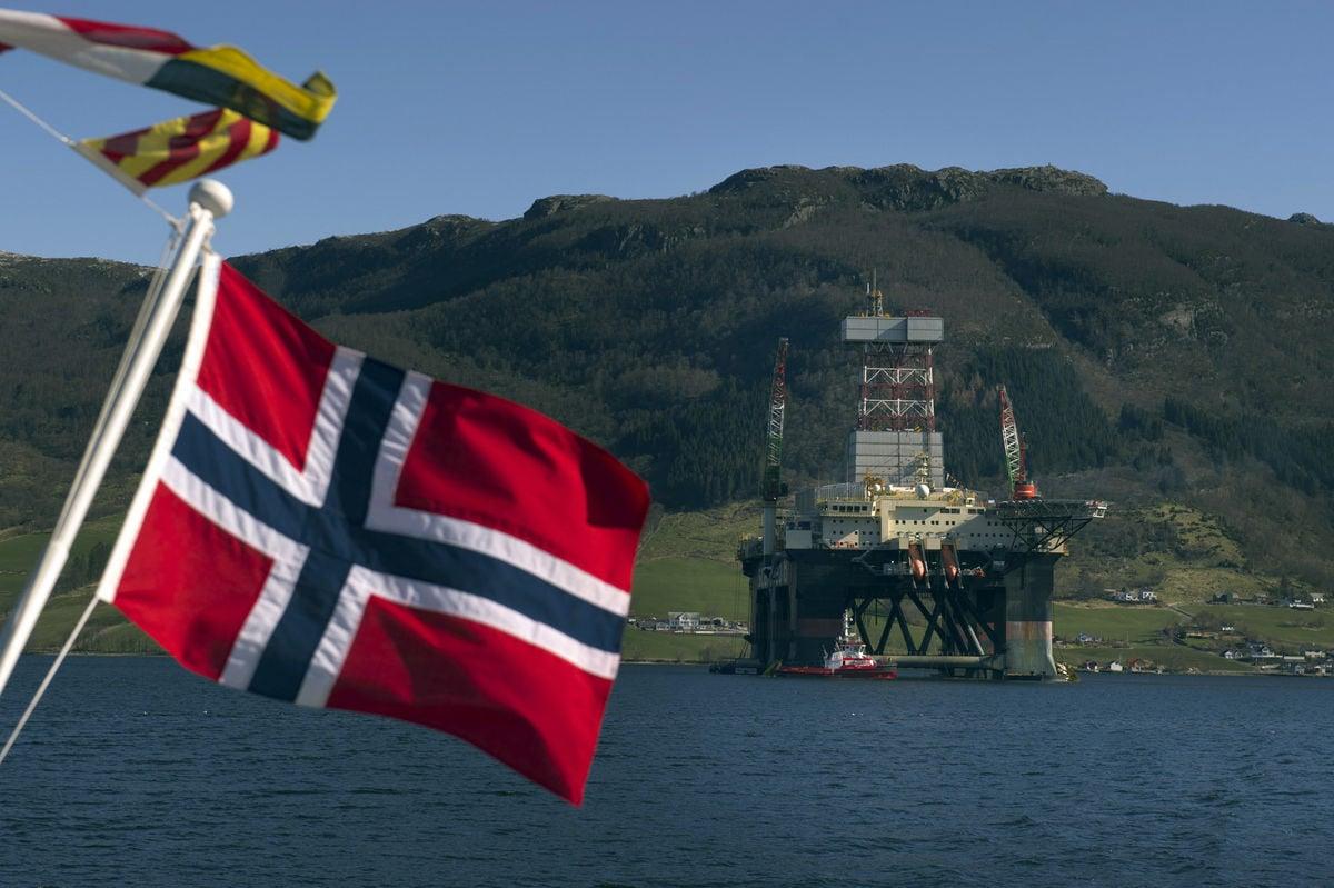 علم النرويج وخلفه حقل نفطي بحري