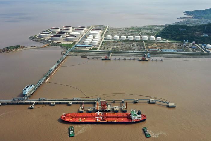 سفينة تحمل الخام ترسو في محطة هوانغتشان بشرق الصين وفي الخلفية صهاريج للتخزين