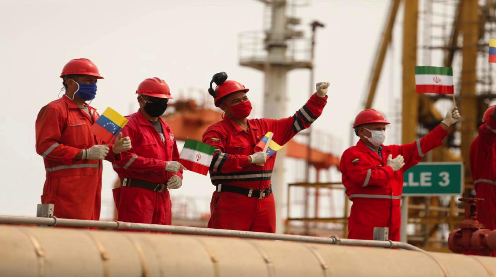 عمال شركة النفط الفنزويلية الحكومية يحملون العلمين الإيراني والفنزويلي بعد وصول شحنة وقود إيرانية إلى مصفاة تكرير
