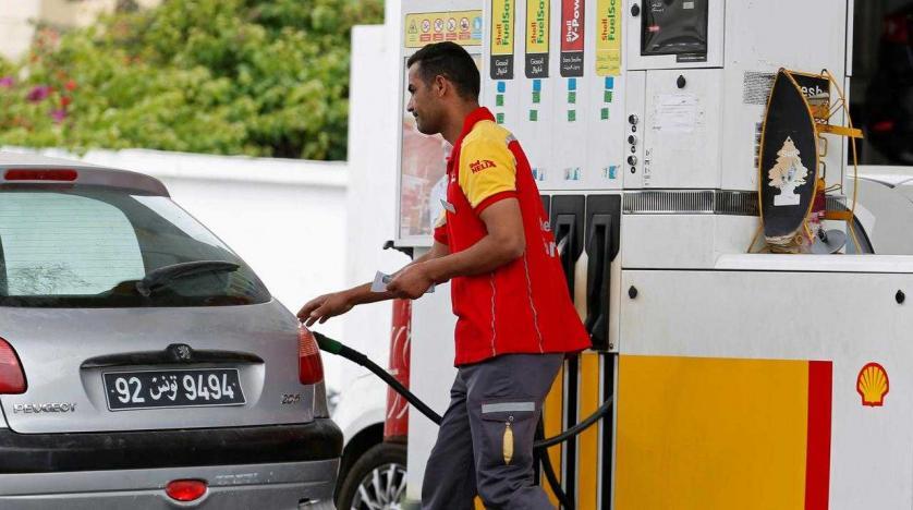 عامل يزود سيارة بالبنزين في محطة وقود بتونس - رفع الدعم عن الطاقة